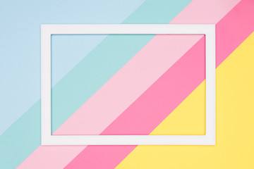 Abstract geometrical pastel blue, pink and yellow paper flat lay background. Minimalism, geometry and symmetry template with empty picture frame mock up.