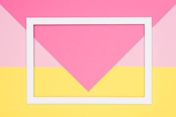 Abstract geometrical pastel pink and yellow paper flat lay background. Minimalism, geometry and symmetry template with empty picture frame mock up.