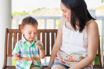 Young Chinese Mother Sitting With Her Mixed Race Chinese and Caucasian Boy Enjoying His Ice Cream Cone