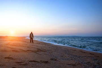 man walking along the beach during a beautiful sunset relaxation time