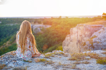 Garden Poster Salmon woman with long hair sitting on a cliff and looking down at sunset travel concept