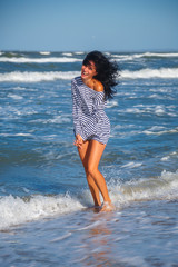cheerful happy girl running around by the sea vacation concept