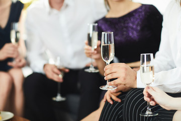 Human hands holding flutes with champagne during conversation at social gathering