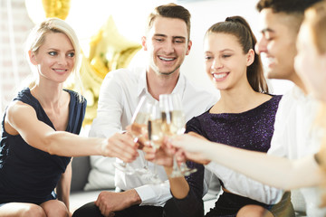 Cheerful friends in elegant clothes toasting with flutes of champagne at party