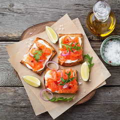 Smoked salmon sandwich with cream cheese on wooden table. top view