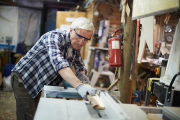 Aged master in protective eyeglasses processing wooden planks on machine in his workshop