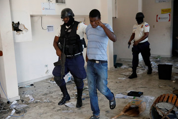 Haitian National Police officers escort out a man found inside a bank office at a commercial area that was looted during protests against fuel price increases in Port-au-Prince