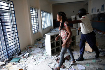 A Haitian National Police officer escorts out a woman found inside a bank office at a commercial area that was looted during protests against fuel price increases in Port-au-Prince