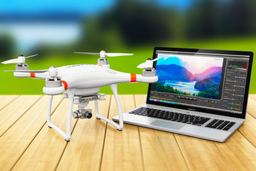 Quadcopter drone and laptop with video software outdoors