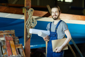Young cheerful engineer in overalls holding two rolled blueprints and notepad
