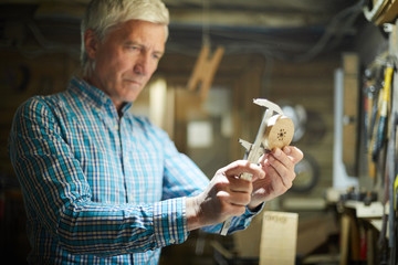 Professional engineer measuring diameter of round wooden workpiece in his workroom