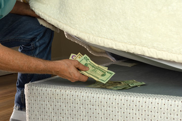 Man stashing putting money under his mattress because he doesn't trust banks and is fearful of financial institutions, this is a bad way to save your money for retirement. There must be a better way!