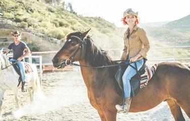 Couple riding horses inside corral ranch