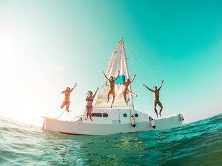 Happy crazy friends diving from sailing boat into the sea