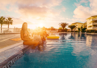 Happy friends drinking champagne in pool party at sunset