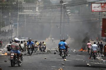 Haitians pass through a barricade on a street in Port-au-Prince