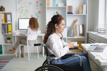 Young office worker in wheelchair having tea or coffee by workplace while watching webcast