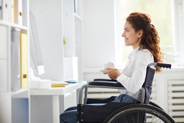 Young female in office attire sitting in wheelchair in front of computer, having tea and watching webcast