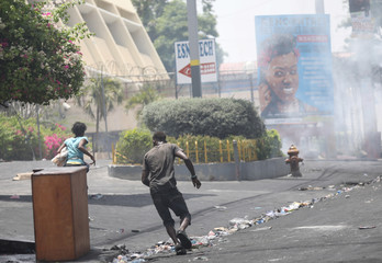 People run away as police uses tear gas to disperse people in a street of Port-au-Prince