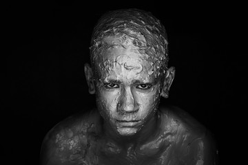 Close-up of a man's face in clay. Monochrome portrait