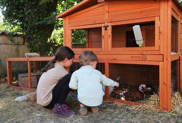 Ein kleiner Junge und ein Mädchen sitzen an einem Kaninchenstall