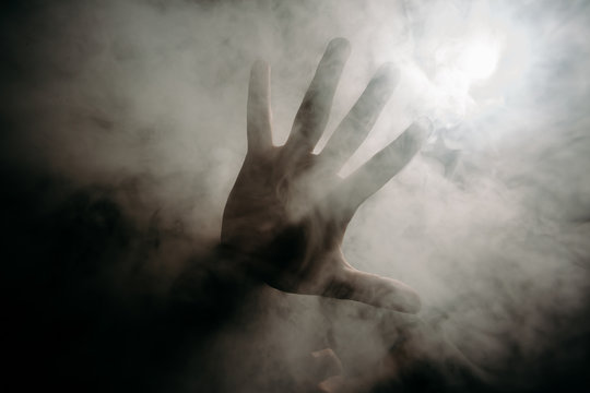 a man's hand in a smoky cloud of hookah in the dark.