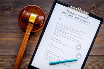Divorce court case. Divorce agreement near wedding rings and judge gavel on dark wooden background top view