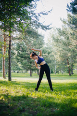 A beautiful girl in the park is engaged in sports. A model with clean skin and oboyatelnoy ulvbkoy in sportswear. Open-air trainings.