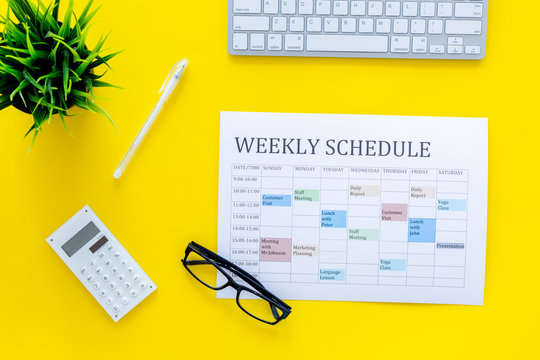 Weekly schedule of manager, office worker, pr specialist or marketing expert. Table with multicolored blocks on yellow office desk with computer, glasses, calculator top view