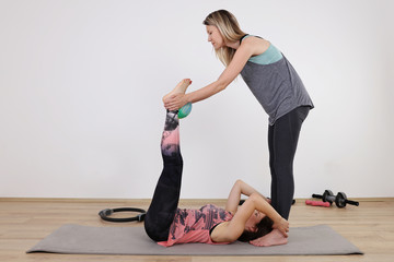 Partner workout. Two female friends doing abs exercises at gym. Sport, fun and friendship concept