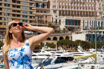 Beautiful blond tourist woman in a blue dress and sunglasses in the port of Monaco.