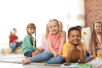 Cute little children with book and blocks indoors. Learning by playing