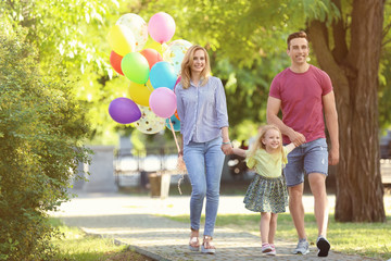 Happy family with colorful balloons in park on sunny day