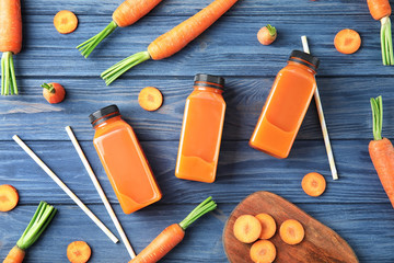 Bottles with carrot juice and fresh vegetable on wooden table, top view