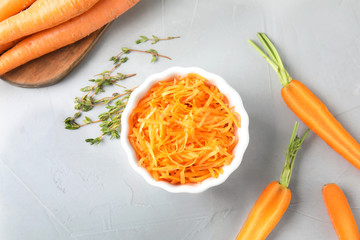 Bowl with grated ripe carrot and fresh vegetable on table, top view