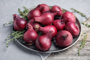 Plate with ripe red onions on table