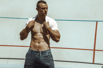Stripped masculine male model street workout on a stadium