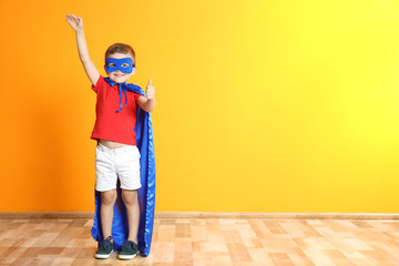 Adorable little child playing superhero indoors