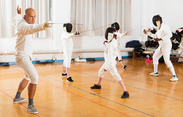 Coach demonstrating fencing movements to kids