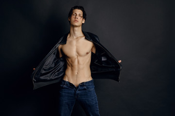 Male model in denim blue jeans and black leather jacket on black background