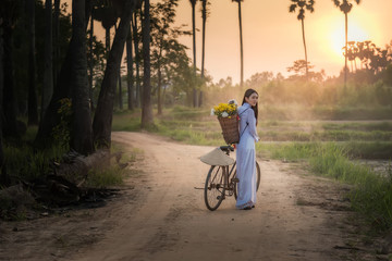 Woman wearing a Vietnamese dress Ao Dai are ride on a bicycle along the road in a village at countryside,Woman Vietnam ride on a bicycle.