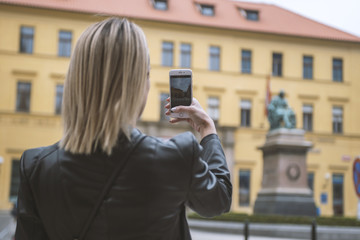 Young girl taking photo with smartphone in European city