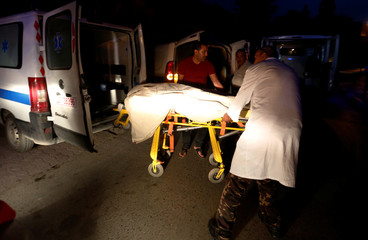 Hospital workers transport the body of member of Tunisian security forces, who was killed in an ambush in the northwest of the country close to the border with Algeria, at a hospital morgue in Tunis
