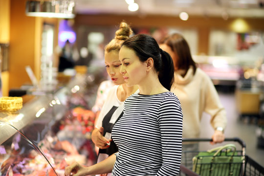 Women shopping for fresh fish seafood in supermarket retail store