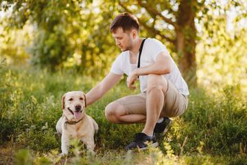 Man owner caressing gently her labrador dog. Concept friendship