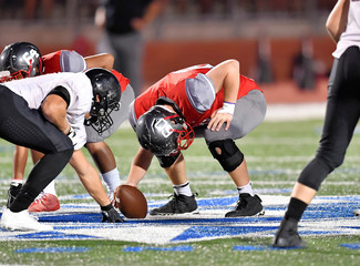 Football lineman blocking and rushing during a football game