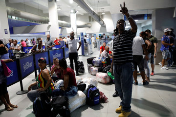 People look at the departures screens at Toussaint Louverture International Airport in Port-au-Prince