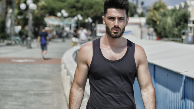 Attractive fit athletic young man soaking in the sun on seaside boardwalk or seafront, wearing black tank-top