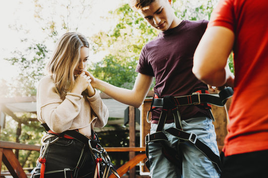 Pretty young woman looking with worry on her man while on him is putted special equipment for ziplining on rope slide.