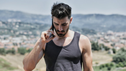 Young handsome man using smartphone, calling someone while standing on a balcony at the seaside over countryside landscape